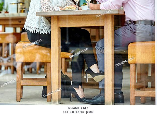 Waist down view of womans high heel shoe touching mans leg at restaurant table