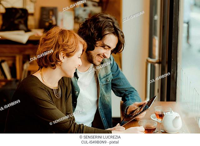 Young couple sitting in cafe, looking at digital tablet