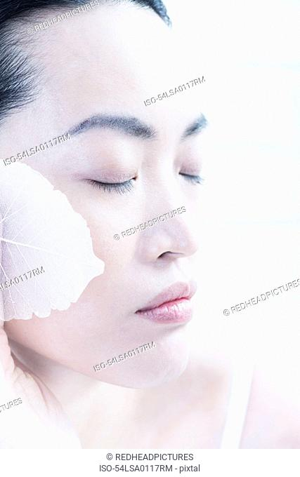 Woman wiping leaves on her face