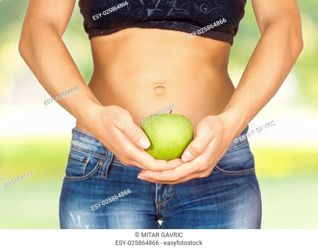 Slim Female with perfect healthy fit body, showing green apple . Caucasian young woman in jeans. Unrecognizable person.Diet and weight loss concept