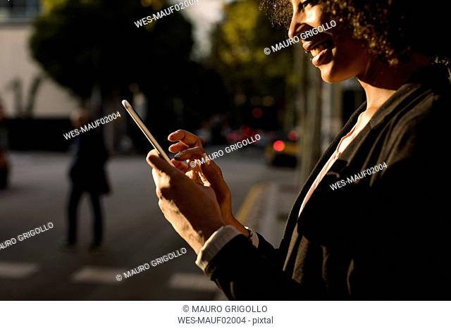 Smiling businesswoman using cell phone on the street at evening twilight, partial view
