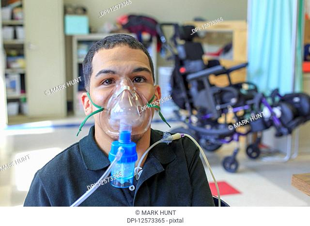 Boy with Spastic Quadriplegic Cerebral Palsy learning at school and using his medical breathing mask