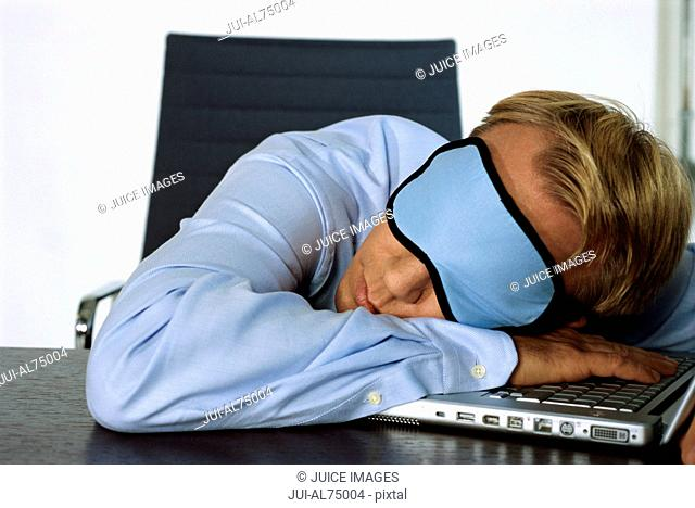 View of businessman sleeping on laptop