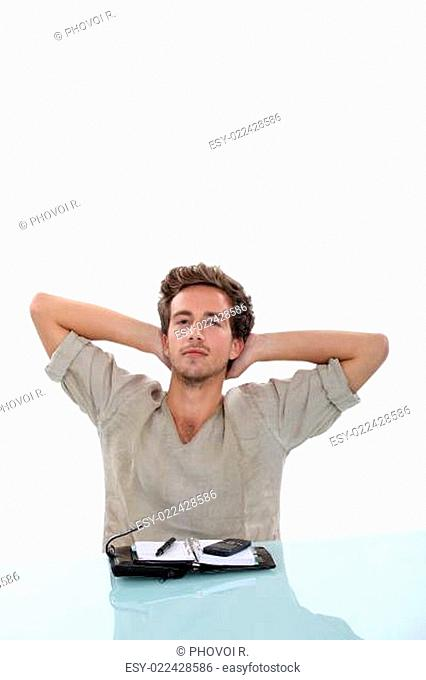 Man stretching his arms behind his head, taking a break from the personal organi
