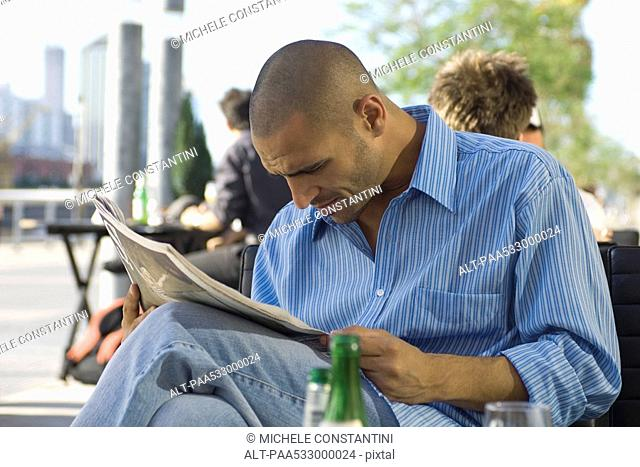Man sitting at sidewalk cafe, reading newspaper
