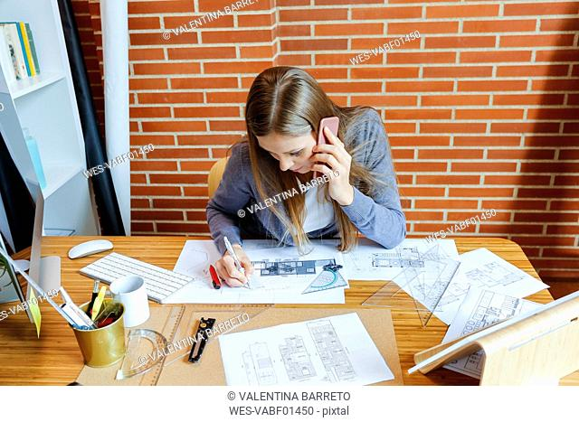 Young woman working in architecture office, talking on the phone