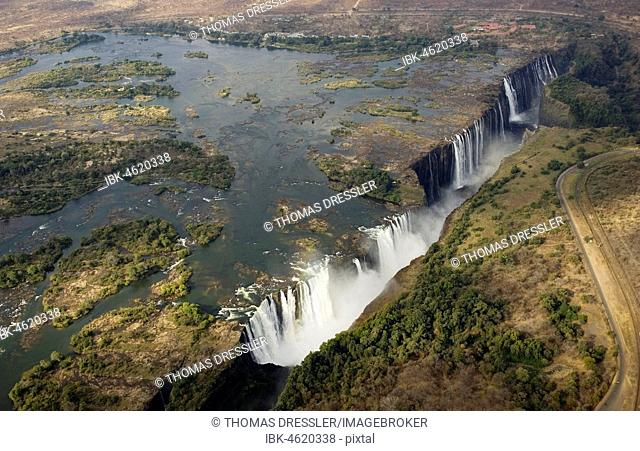 Aerial view of the Zambezi River and the Victoria Falls, in the foreground the Main Falls in Zimbabwe, behind the Rainbow Falls and the Eastern Cataract in...
