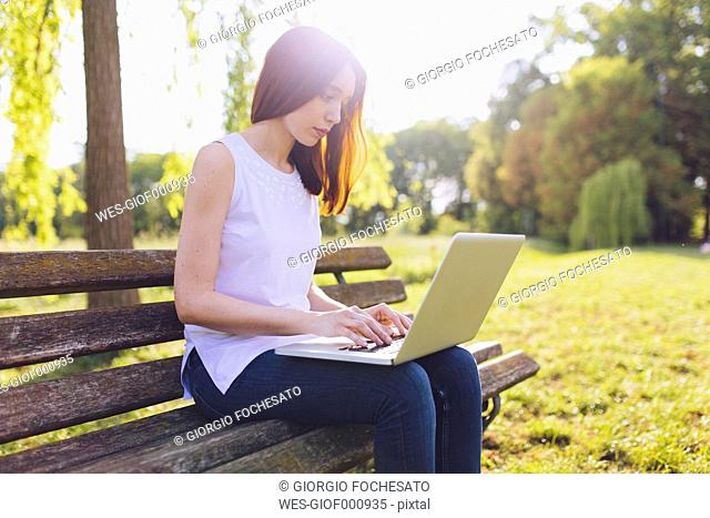 Woman learning at the laptop while sitting on a bench at the park