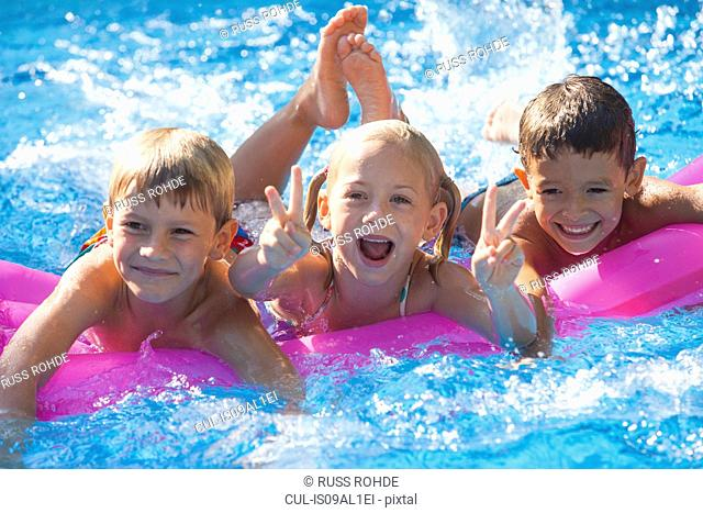 Portrait of three children playing on inflatable mattress in garden swimming pool