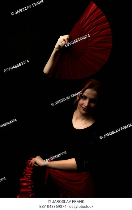 Low Key portrait of young woman dancing flamenco holding red fan over head. All on the dark background