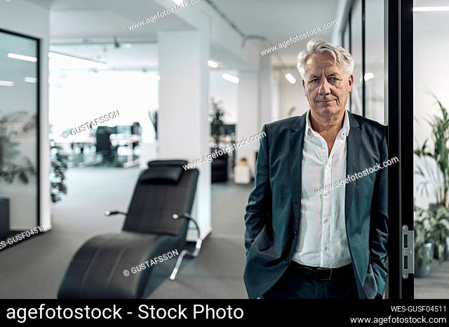 Businessman with hands in pockets leaning on wall at office