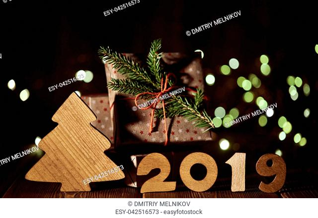 Wooden fir tree, gift boxes and text 2019 from wooden figure on dark wooden background with LED light garland. Horizontal view. New Year and Christmas