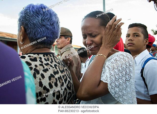 Santiago de Cuba, Cuba - 04.12.2016. A woman (foreground right) is weeping right after Fidel Castro's ashes passed on their way from Plaza Maceo towards their...