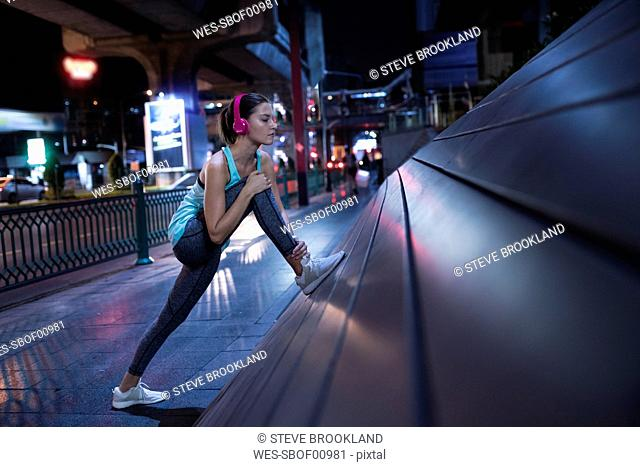Young woman with pink headphones stretching in the street