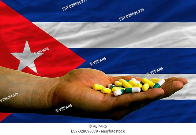 man holding capsules in front of complete wavy national flag of cuba symbolizing health, medicine, cure, vitamines and healthy life