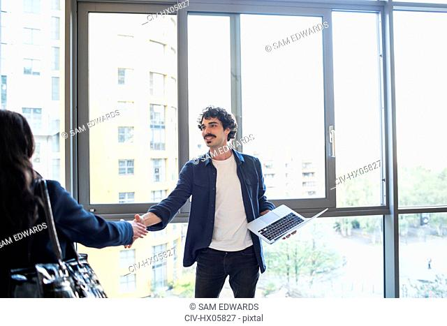 Businessman and businesswoman shaking hands at urban office window