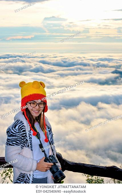 Woman tourist holding a DSLR camera on beautiful nature landscape of fog is like the sea in the winter during sunrise background at high viewpoint Phu Ruea...