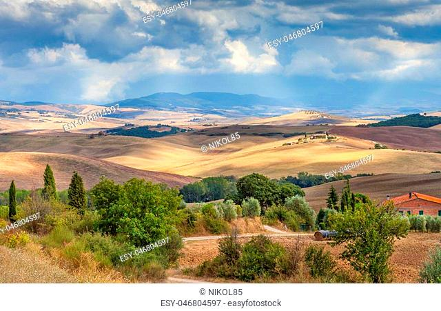 Rural landscape of Tuscany, Italy. The fields, hills and forests, the sun's rays make their way through the clouds. Agriculture