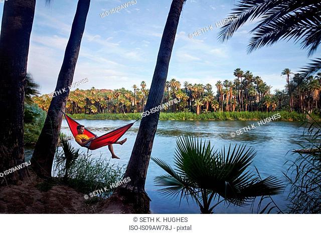 Man relaxing in hammock by lake, Baja California, Mexico