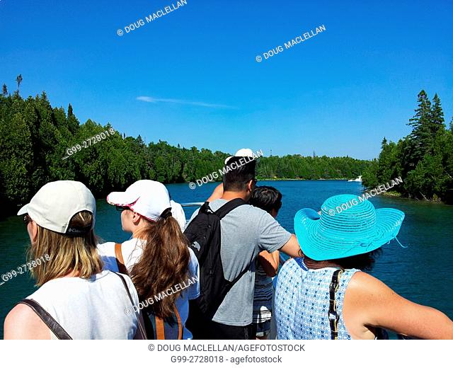 Six tourists on a cruise ship look at trees and an island during a tour of Fathom Five National Marine Park on Georgian Bay, Ontario, Canada