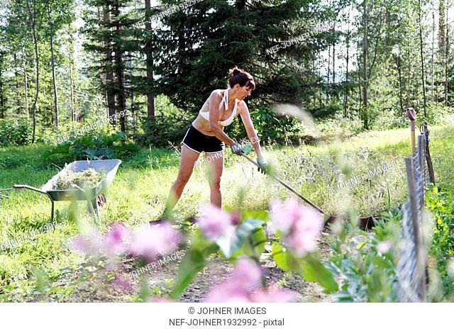 Woman working in garden, Norrbotten, Sweden