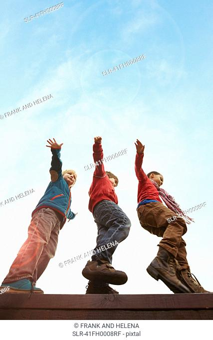 Children balancing on wooden wall
