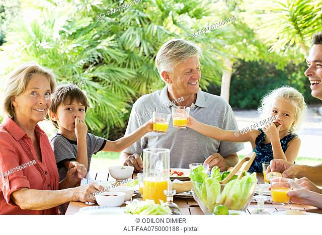 Multi-generation family enjoying meal outdoors
