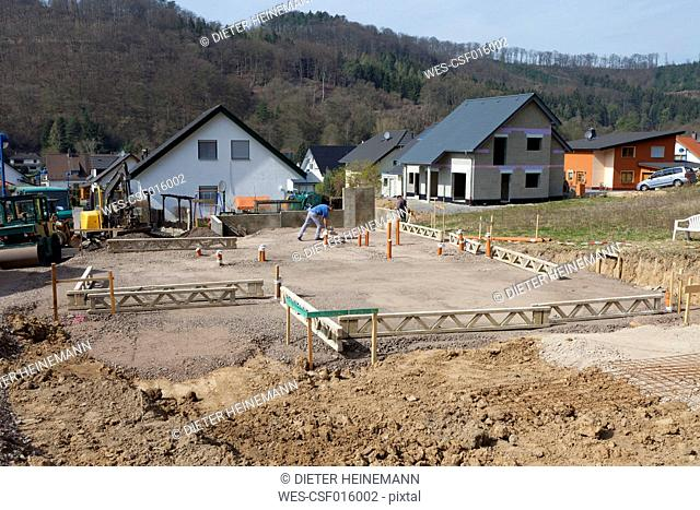 Germany, Rhineland-Palatinate, house building, earth works, laying pipes before pouring the concrete of foundation