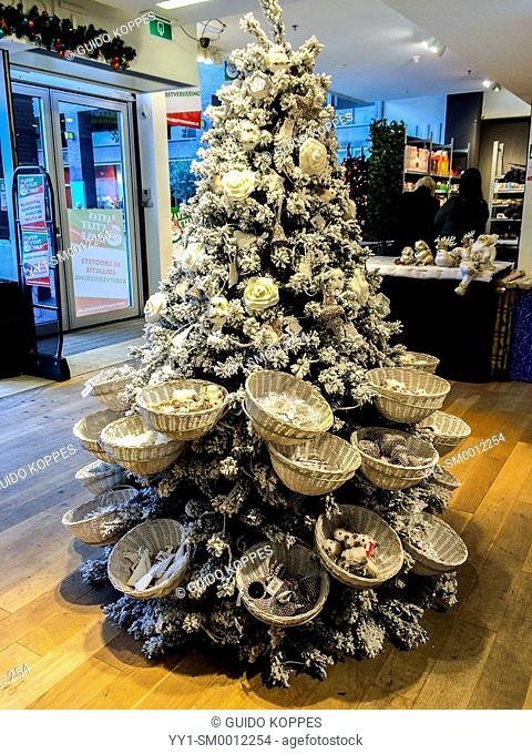 Tilburg, Netherlands. Artificial cristmas tree installed at an outlet store with cristmas items for sale