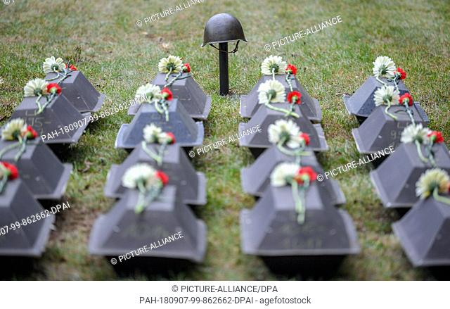 07.09.2018, Brandenburg, Lebus: A Soviet steel helmet from the Second World War can be seen in front of small coffins with the mortal remains of killed Red Army...