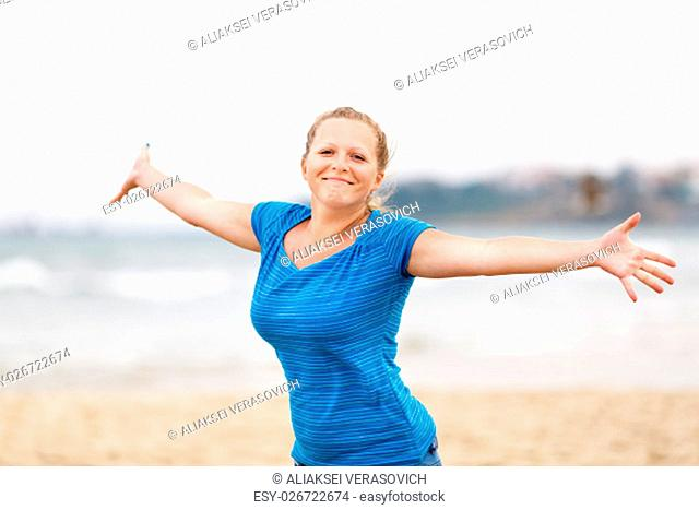 Beautiful young woman enjoying freedom. Free happy girl posing arms outstretched to the side and looking at the camera