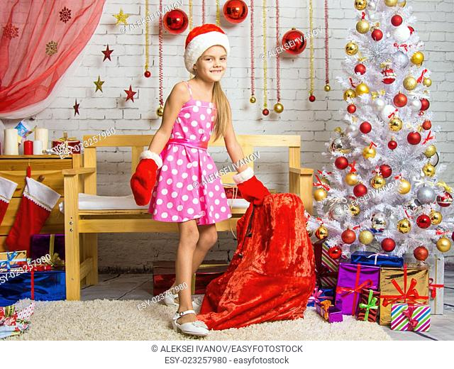 Cheerful little girl playing and having fun with a bag of gifts in the home New Years interior