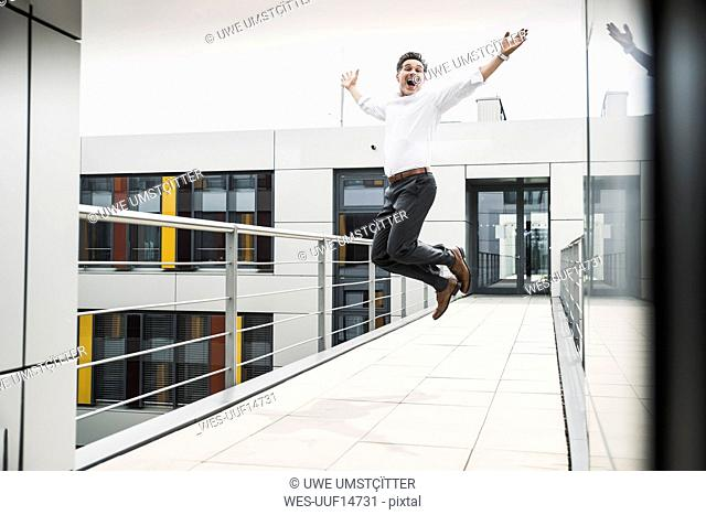 Cheering businessman jumping on skywalk at office building