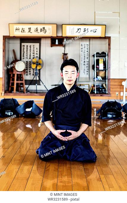 Male Japanese Kendo fighter kneeling on wooden floor, meditating