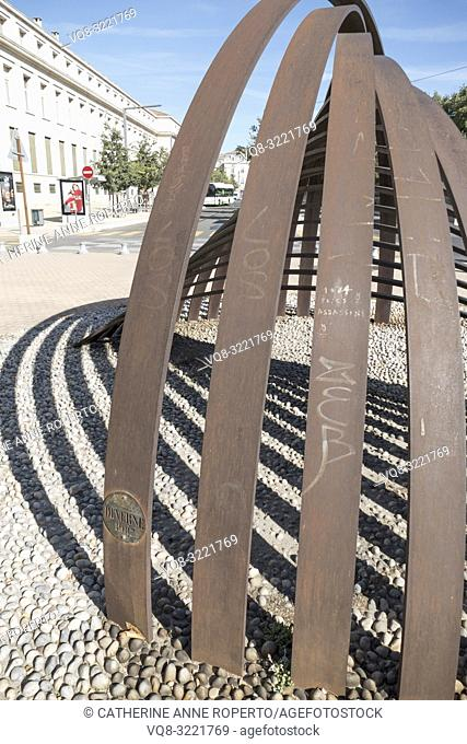Curved linear sculpture in bronze forms a reverberating bell shape and echoing shadows on the pebbled pavement near Avignon Train Station, Vaucluse, Provence