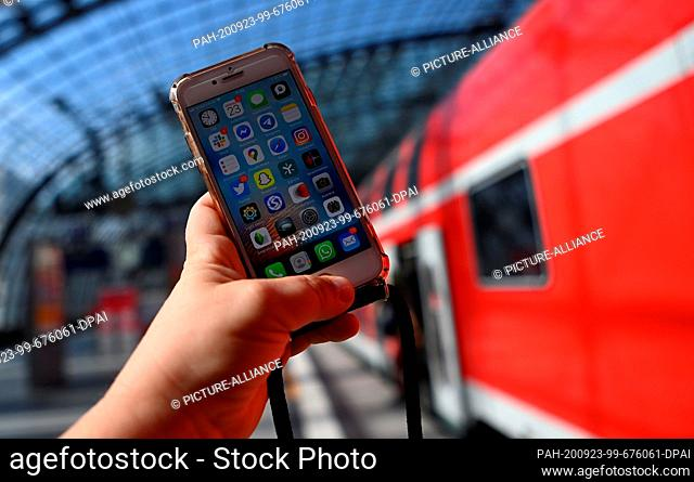 ILLUSTRATION - 23 September 2020, Berlin: A woman is holding a mobile phone in her hand at Berlin Central Station. Rail customers and visitors can now dial into...