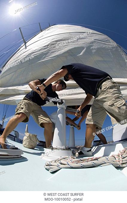 Sailors operating windlass on yacht low angle view wide angle lens