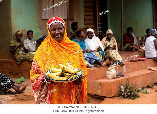 Smiling Muslim lady with bright headscarf, holding basket of bananas, at ladies co-operative, Rwanda