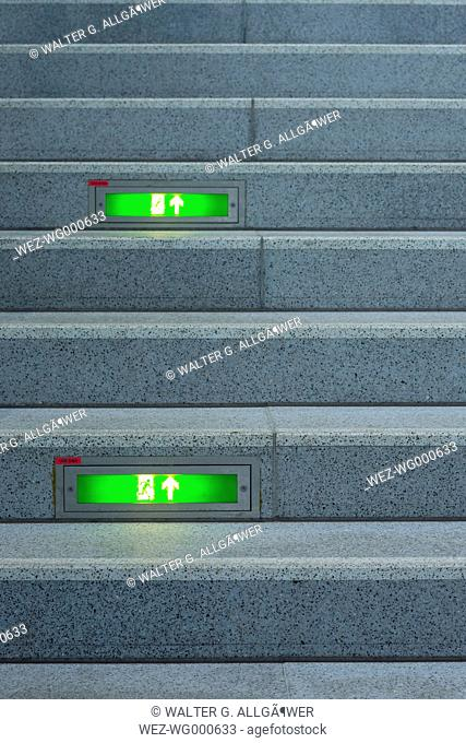 Public stairway with green emergency exit signs