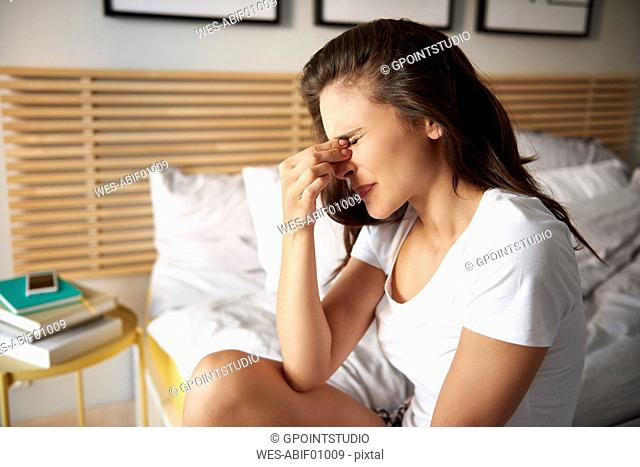 Young woman sitting on bed suffering from headaches