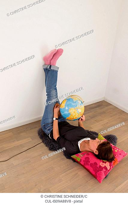 Woman lying on floor of empty room holding globe