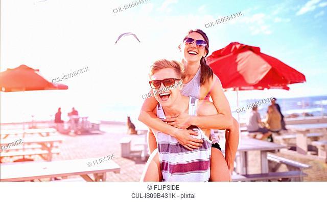 Man giving smiling woman piggyback