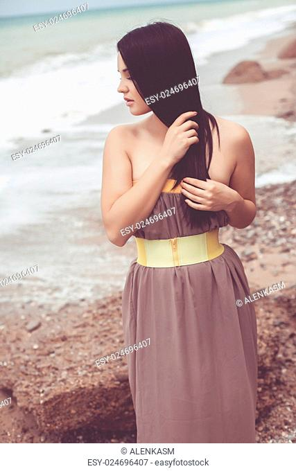Outdoor portrait of a gorgeous fashion model dressed in maxi chiffon dress posing at the beach