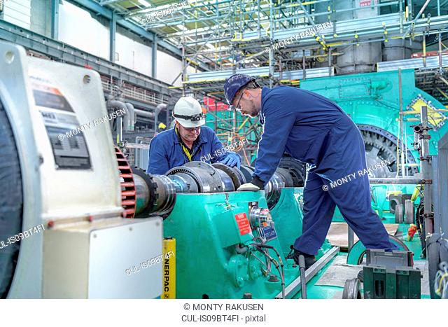 Engineers inspecting gears at generator end in nuclear power station during outage
