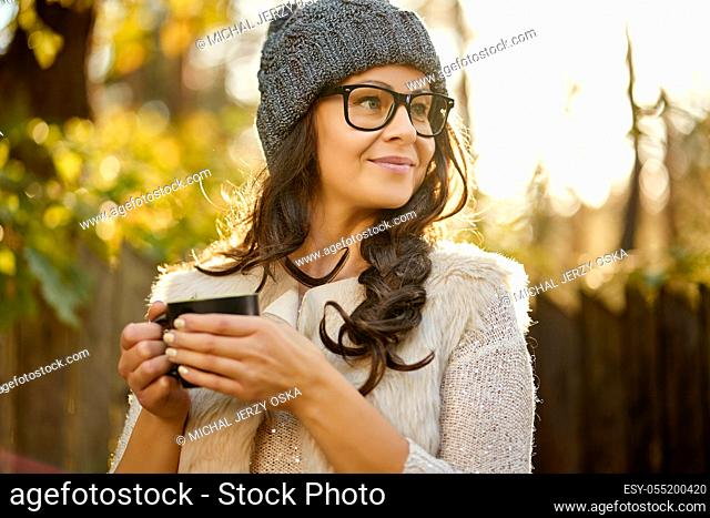 beautiful woman in a cap and glasses holds in her hand a cup of coffee in an autumn forest