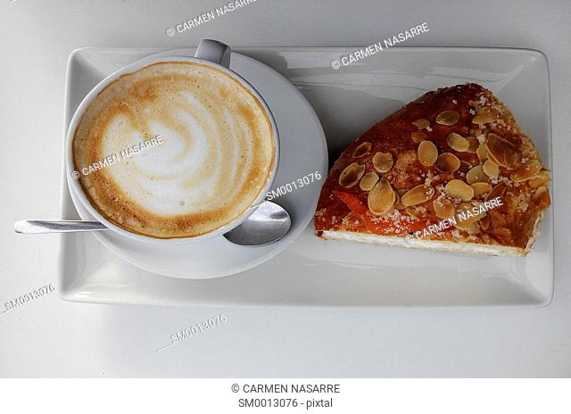 Coffee with milk and cake almonds