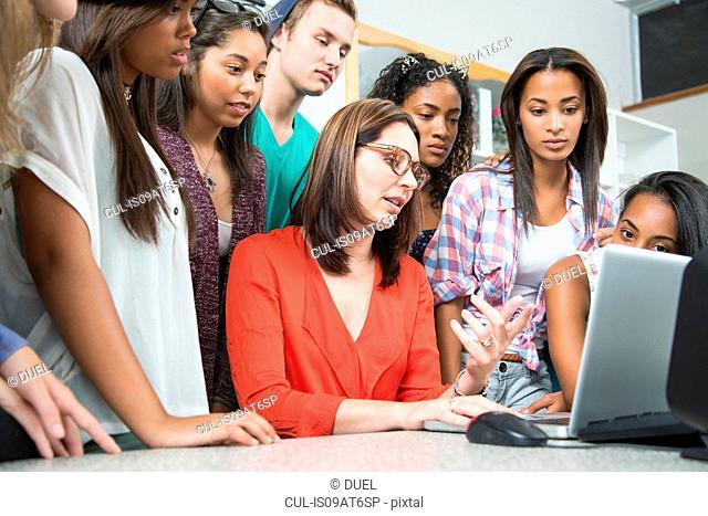 Mid adult female teacher explaining on laptop to high school students