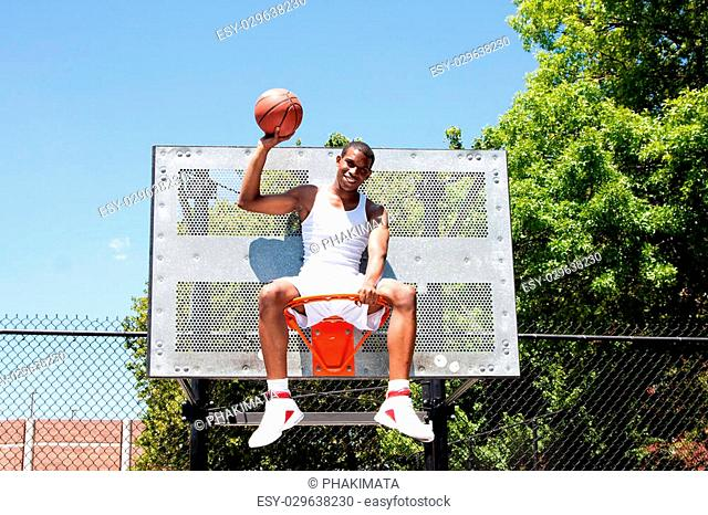 Happy smiling handsome sporty African-American male basketball player dressed in white and holding his ball with one hand outdoor on a summer day in a...