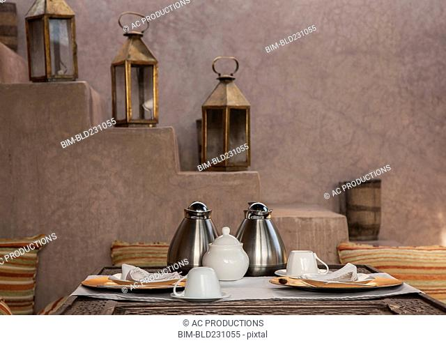 Coffee pots and plate at table near staircase