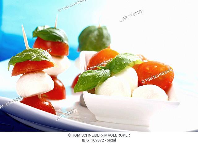 Tomato-mozzarella sticks with basil on a dish